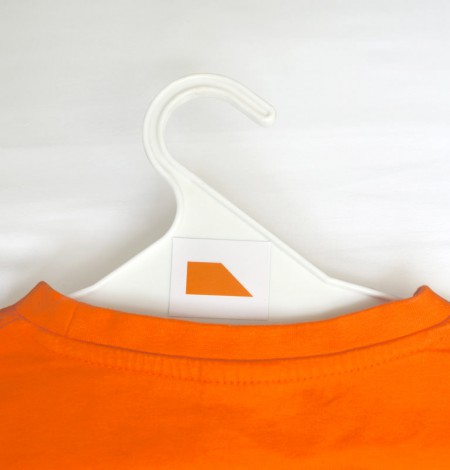 Orange sticker label applied to a clothes hanger with an orange t-shirt