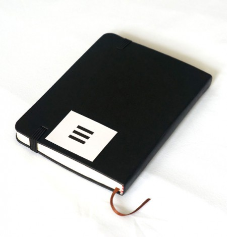 Black sticker label applied to a black notebook